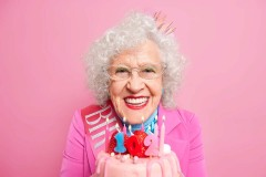Portrait of lovely grandmother with makeup celebrates 102nd birthday blows candles on bday cake smiles gladfully wears festive clothes has party isolated over pink background. Festive event concept