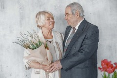 Senior couple embracing isolated on grey in studio